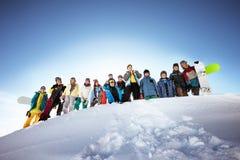 Gruppe Skifahrer und Snowboarder Stockbilder