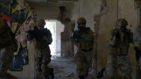 Gruppe Soldaten, die schnell durch das ruinierte Gebäude in der Suche und im Rettungseinsatz umziehen stock video