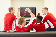 Gruppe Sport-Fans, die im Fernsehen Spiel zu Hause aufpassen Stockbild