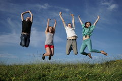 Gruppe springende Leute auf grean Wiese Stockbild