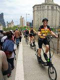 Gruppe Stellung von den elliptischen Radfahrern, die auf eine gedrängte Brooklyn-Brücke fahren Mai 2018 stockfoto