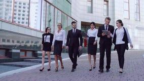 Gruppe stilvolle Geschäftsleute, die zusammen hinunter die Straße zu ihrem Geschäftszentrum gehen stock video