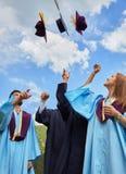Gruppe Studenten in den Staffelungskleidern und -kappen Stockfotos