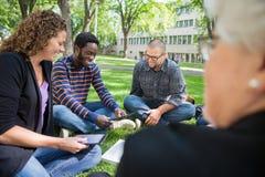 Gruppe Studenten, die auf dem Campus Digital-Tablet verwenden Stockfotos