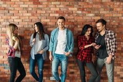 Gruppe Studenten, die an der Backsteinmauer stehen stockbild