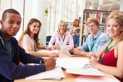 Gruppe Studenten, die in der Bibliothek mit Lehrer zusammenarbeiten Stockfotografie