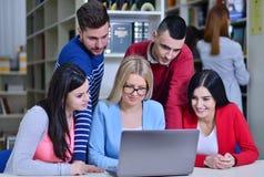 Gruppe Studenten, die in der Bibliothek mit Lehrer zusammenarbeiten Stockbild