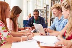 Gruppe Studenten, die in der Bibliothek zusammenarbeiten Stockbilder