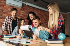 Gruppe Studenten, die zusammen auf Laptop schauen lizenzfreie stockfotografie