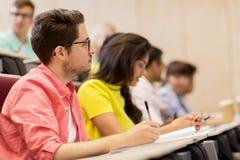 Gruppe Studenten mit Notizbüchern im Vorlesungssal stockfotografie