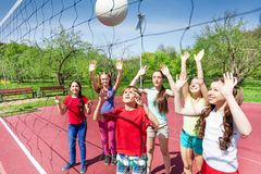Gruppe Teenager, der Volleyball nahe dem Netz spielt Lizenzfreie Stockfotos