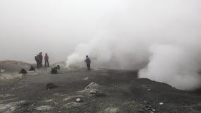 Gruppe Touristen fotografierte rauchende Fumarole im aktiven Vulkan des Kraters stock footage