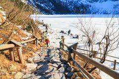 Gruppe Touristen gehen auf den gefrorenen Morskie Oko See, Polen Lizenzfreies Stockbild