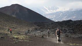Gruppe Touristen und Reisende, die auf Spur auf Hintergrund des vulkanischen Kegels und des Lavaflusses gehen stock footage
