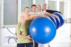 Gruppe tragende Turnhallenbälle der älteren Leute Lizenzfreies Stockbild