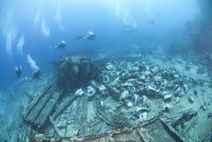 Gruppe Unterwasseratemgerättaucher, die ein Schiffswrack erforschen. lizenzfreies stockfoto