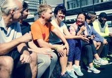 Gruppe verschiedene Athleten, die zusammen an der Turnhalle sitzen stockfotografie