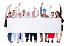Gruppe verschiedene Berufsleute mit einer Fahne Stockfotografie