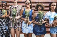 Gruppe verschiedene Frauen, die Ananas zusammenhalten stehen Stockfoto