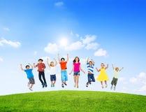 Gruppe verschiedene Kinder, die draußen springen Stockbilder