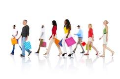 Gruppe verschiedene Leute, die mit Einkaufstaschen gehen lizenzfreie stockfotografie