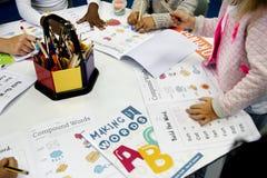 Gruppe verschiedene Studenten, die Arbeitsbuch in der Klasse färben lizenzfreie stockbilder