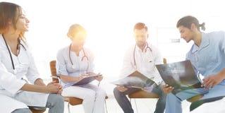 Gruppe von den Chirurgen und von medizinischem Berufspersonal, die auf geduldiger Radiographie sich besprechen lizenzfreies stockbild