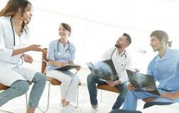 Gruppe von den Chirurgen und von medizinischem Berufspersonal, die auf geduldiger Radiographie sich besprechen stockfotografie