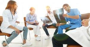 Gruppe von den Chirurgen und von medizinischem Berufspersonal, die auf p sich besprechen lizenzfreies stockbild