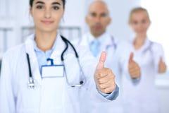 Gruppe von Doktoren, die O.K. darstellen oder von Zustimmungszeichen mit dem Daumen oben Hohe Stufe und ärztliche Bemühung der Qu Stockbilder