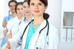 Gruppe von Doktoren, die O.K. darstellen oder von Zustimmungszeichen mit dem Daumen oben Hohe Stufe und ärztliche Bemühung der Qu Lizenzfreie Stockbilder