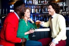 Gruppe von drei Freunden in einem trinkenden Bier der Bar Lizenzfreie Stockfotos