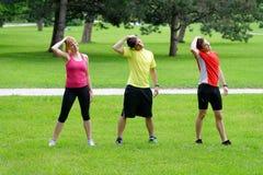 Gruppe von drei jungen Athleten, die Übung ausdehnend tun Stockfotografie