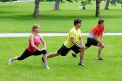 Gruppe von drei jungen Athleten, die Übung ausdehnend tun Lizenzfreies Stockfoto