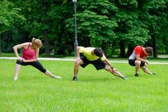 Gruppe von drei jungen Athleten, die Übung ausdehnend tun Stockbilder
