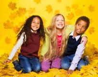 Gruppe von drei Kindern, die auf dem Herbstlaub sitzen Lizenzfreie Stockfotos