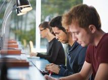 Gruppe von drei Leuten in der Bibliothek Stockfoto