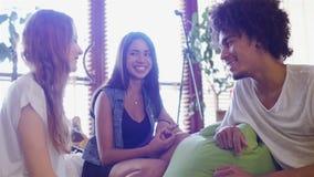 Gruppe von drei Leuten, die auf der Couchunterhaltung sitzen stock video