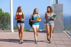 Gruppe von drei Studentenjugendlichen, die in Richtung zur Kamera gehen Stockfotografie
