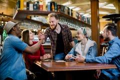 Gruppe von fünf Freunden, die eine Sitzung im Café zusammen haben Zwei Frauen und drei Männer am Unterhaltungsc$lachen des Cafés  lizenzfreie stockfotografie