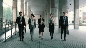 Gruppe von fünf Geschäftsleuten gefiel und überzeugtes Gehen in Geschäftszentrumsäulengang stock video footage