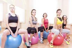 Gruppe von fünf kaukasischen weiblichen Athleten, die Übungen mit Fitballs in der Turnhalle haben stockfotos