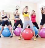 Gruppe von fünf kaukasischen weiblichen Athleten, die Übungen mit Fitballs in der Turnhalle haben stockfotografie