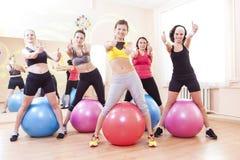 Gruppe von fünf kaukasischen weiblichen Athleten, die Übungen mit Fitballs in der Turnhalle und im Darstellen haben stockfotos
