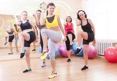 Gruppe von fünf kaukasischen weiblichen Athleten, die Übungen zusammen ausdehnen in der Turnhalle haben lizenzfreies stockbild