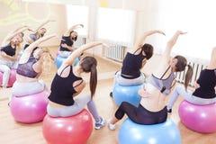 Gruppe von fünf kaukasischen weiblichen Athleten, die das Ausdehnen von Übungen haben stockfotografie