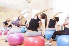 Gruppe von fünf kaukasischen weiblichen Athleten, die das Ausdehnen von Übungen haben stockbild