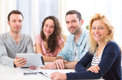 Gruppe von 4 jungen attraktiven Leuten, die an einem Laptop arbeiten Lizenzfreies Stockfoto