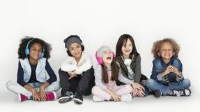 Gruppe von Kinderstudio-lächelnden tragenden Kopfhörern und von Winter C stockfotografie