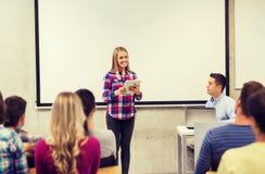 Gruppe von lächelnden Studenten und von Lehrer im Klassenzimmer stockfotografie